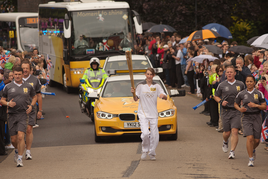 Flanked by the Torch Security Team, Abi Grainger holds the torch aloft