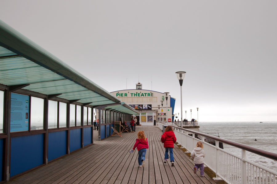 The girls running back down the pier