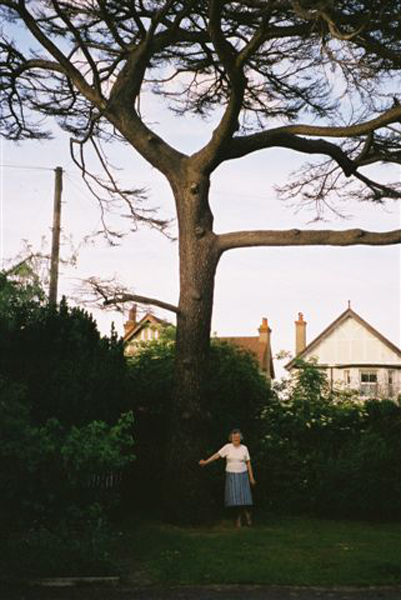 Grandma with the old cedar tree before it was cut down